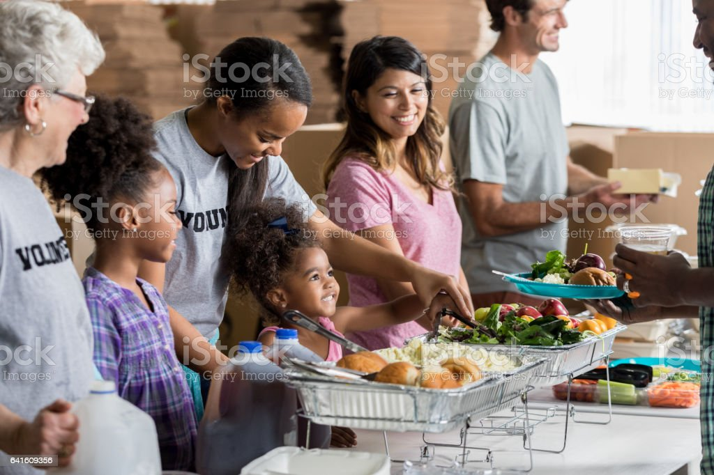 Diverse group of happy volunteers serve meals in homeless shelter stock photo