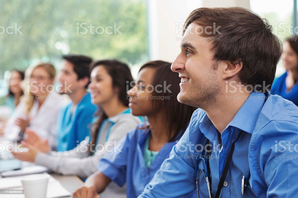 Diverse group of medical sudents listening intently in college classroom stock photo
