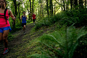 Diverse group of outdoor enthusiasts running in the woods