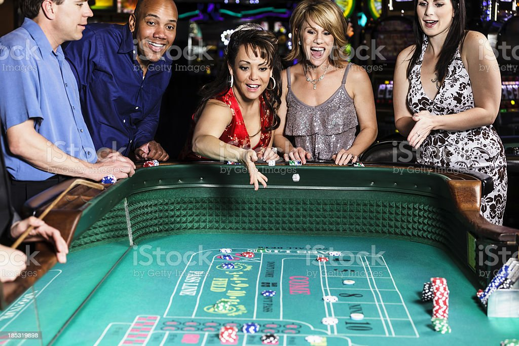 Diverse Group of People Playing Craps In Casino stock photo