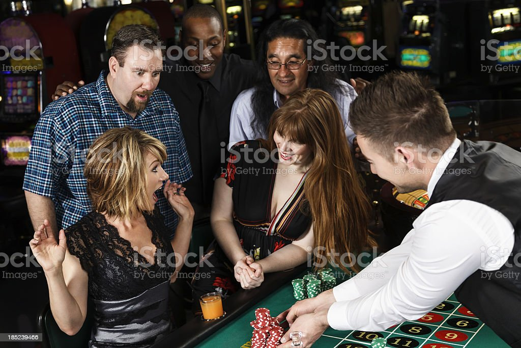 Diverse Group of People Playing Roulette In a Casino royalty-free stock photo