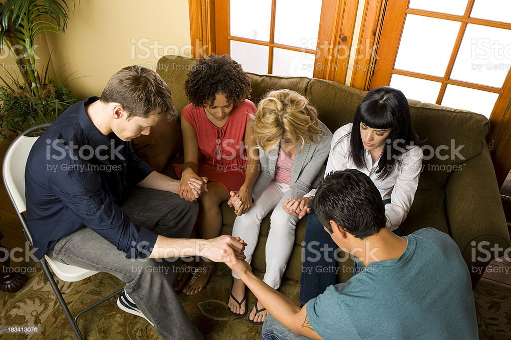 Diverse group of people praying royalty-free stock photo