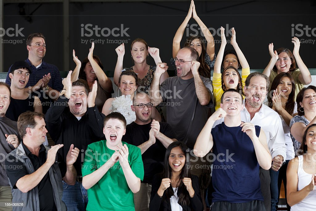 Diverse group of people standing and cheering at the game royalty-free stock photo