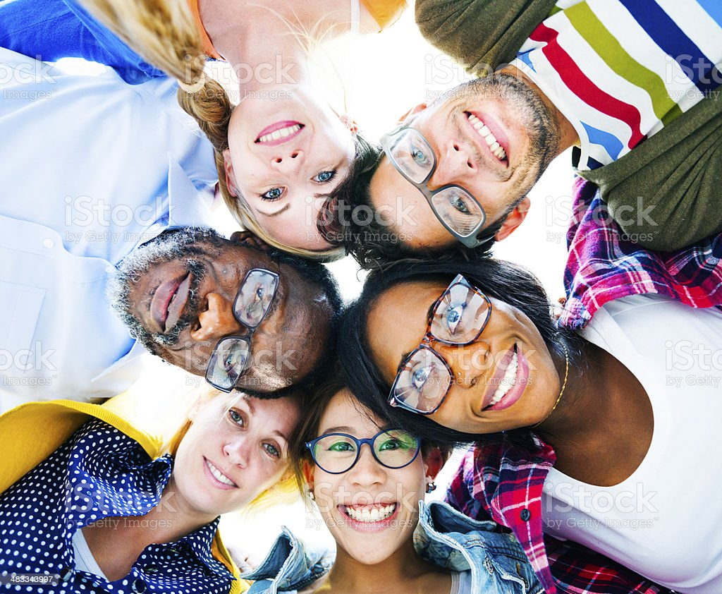 Diverse Group of People with their Heads Together Showing Friendship stock photo