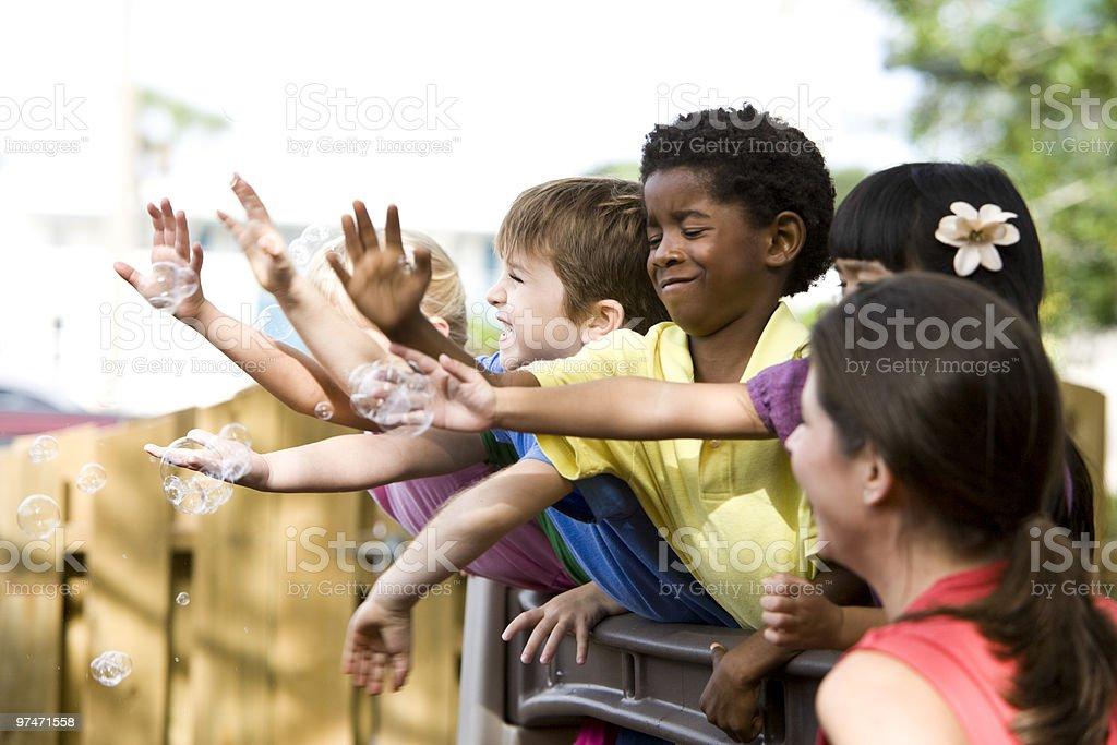 Diverso grupo de preescolar niños jugando en cuidados diurnos para con el maestro foto de stock libre de derechos