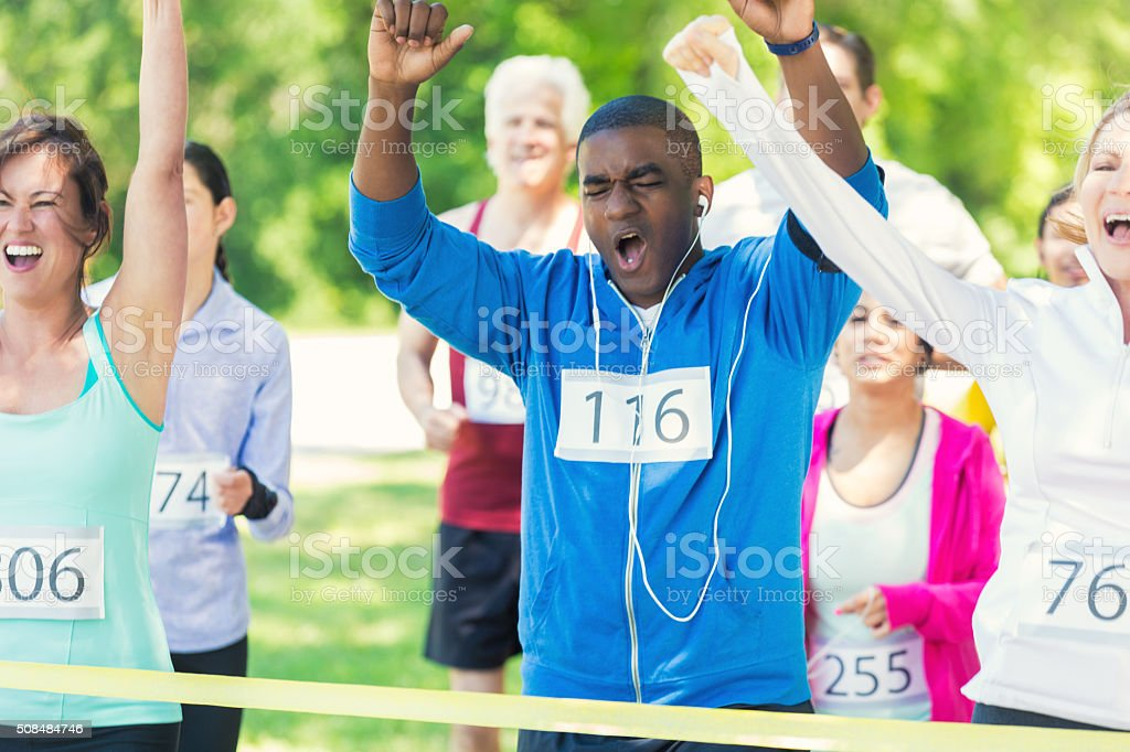 Diverse group of runners celebrate at finish line stock photo