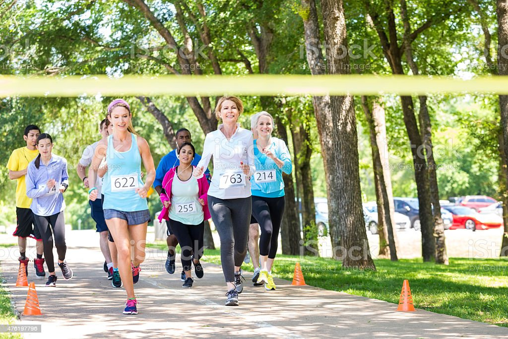 Diverse group of runners racing toward marathon finish line stock photo