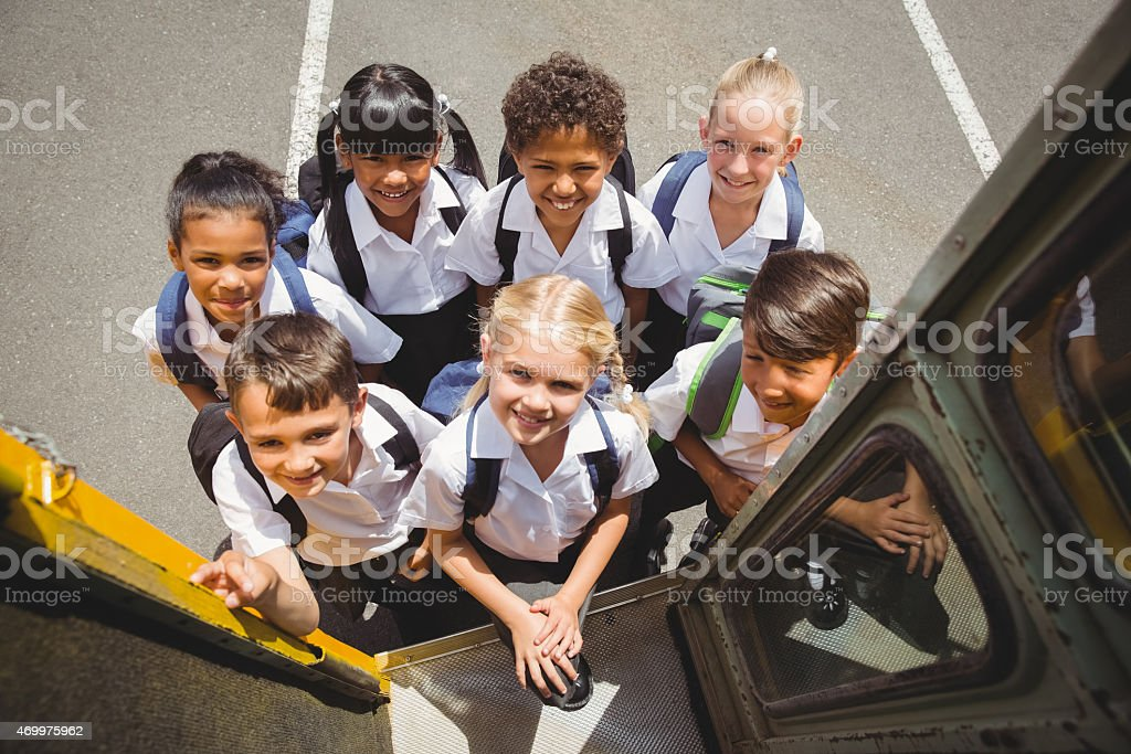 Diverse group of schoolchildren getting on the school bus stock photo