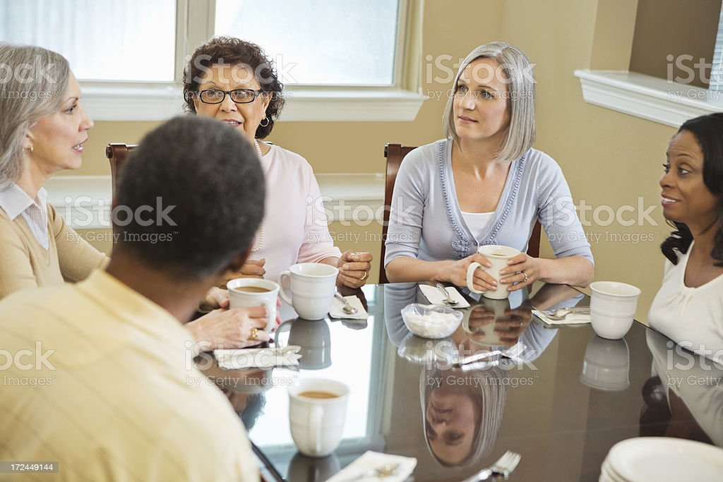 Diverse group of senior friends enjoying coffee together royalty-free stock photo