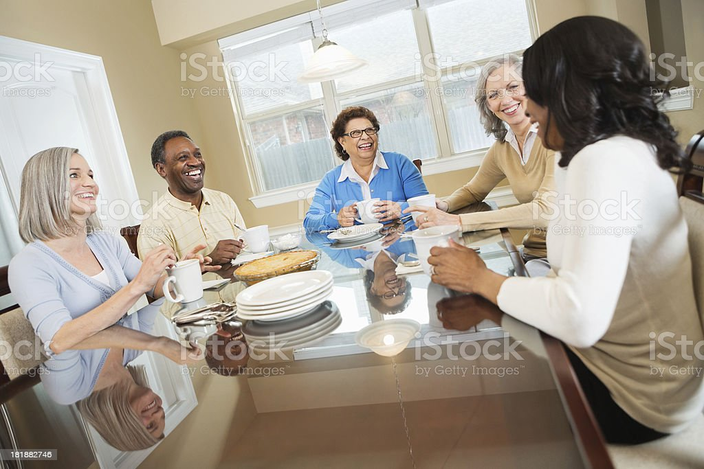 Diverse group of senior friends having coffee in dining room royalty-free stock photo