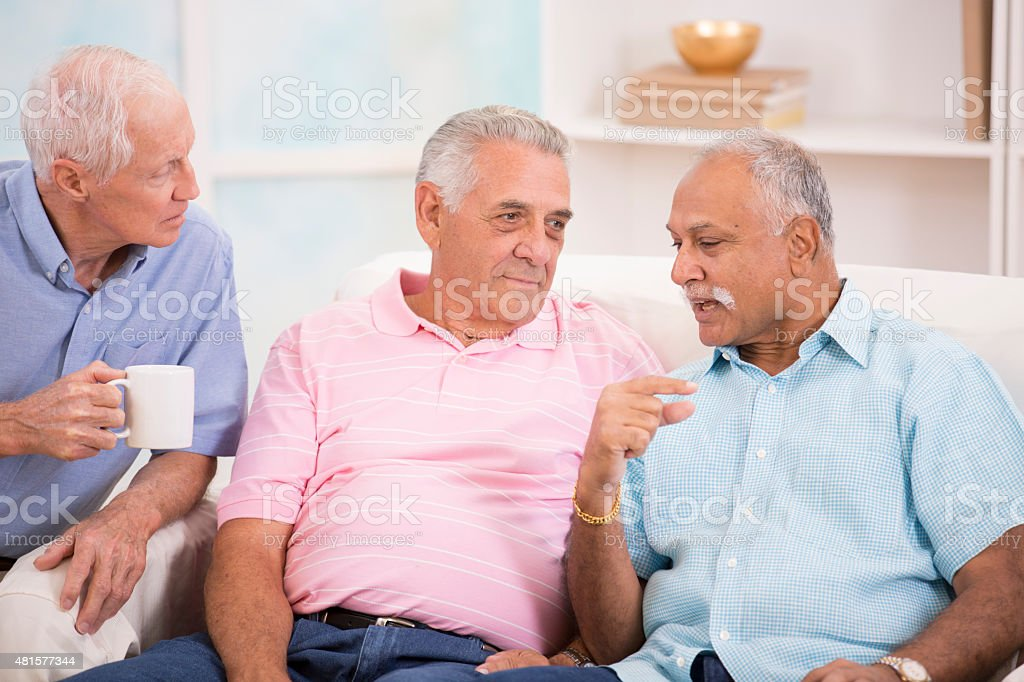 Diverse group of senior men console a friend. Home setting. stock photo