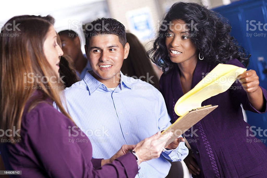 Diverse group of teachers in discussion at school locker area royalty-free stock photo