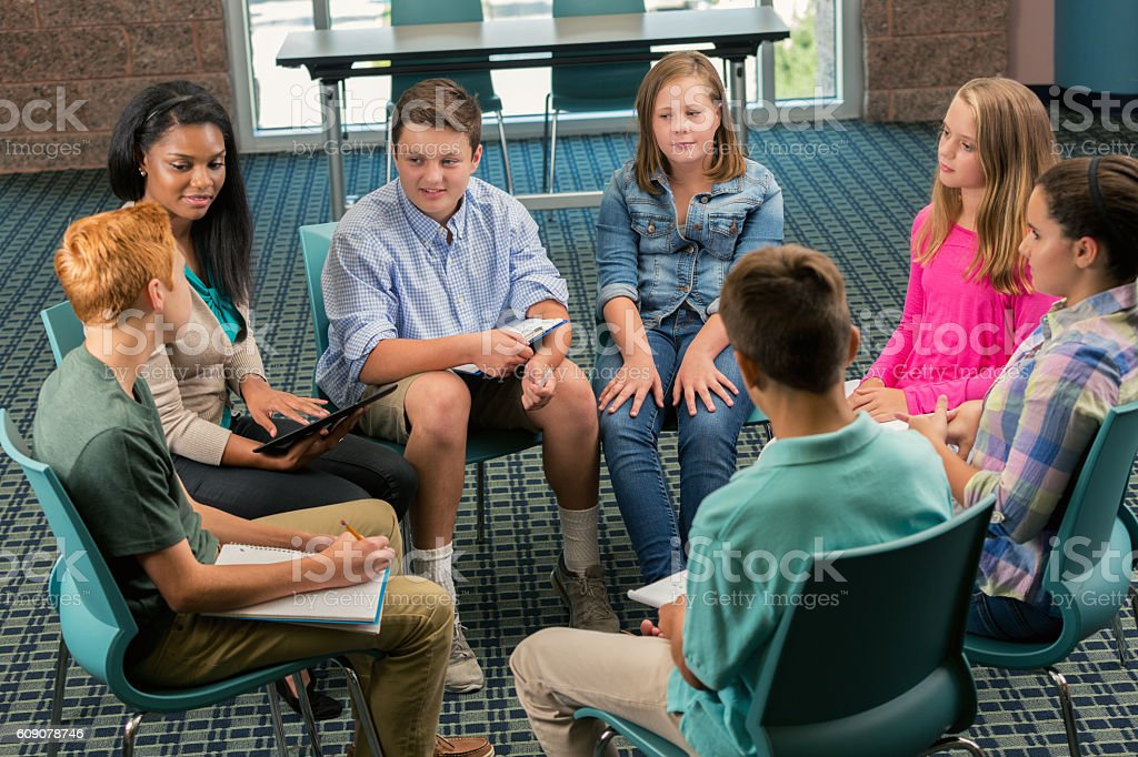 Diverse group of teens participate in group therapy stock photo
