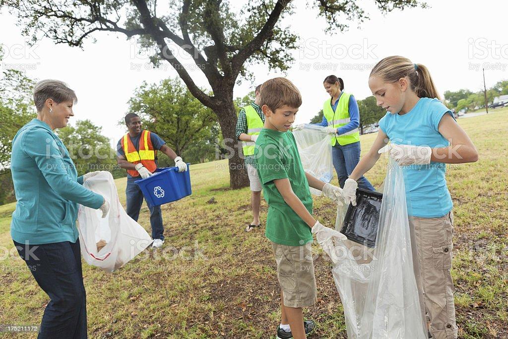 Diverse group of volunteers picking up garbage/ environmental responsibility stock photo