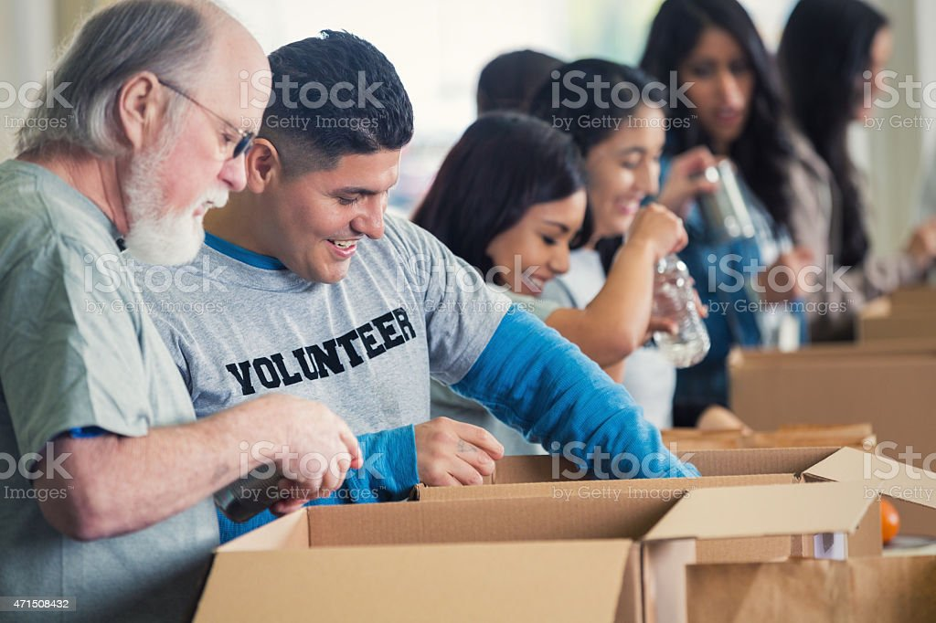 Diverse group of volunteers sorting donated groceries at food bank stock photo