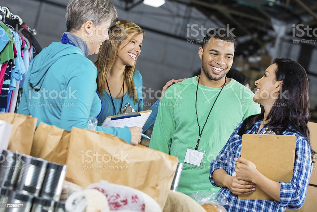 Diverse group of volunteers sorting donations at food bank royalty-free stock photo