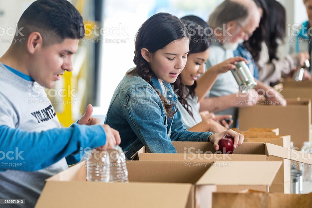 Diverse group of volunteers sorting food donations into boxes stock photo