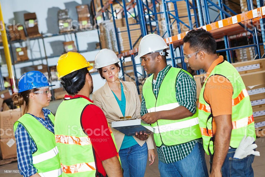 Diverse group of warehouse workers reviewing job with manager royalty-free stock photo