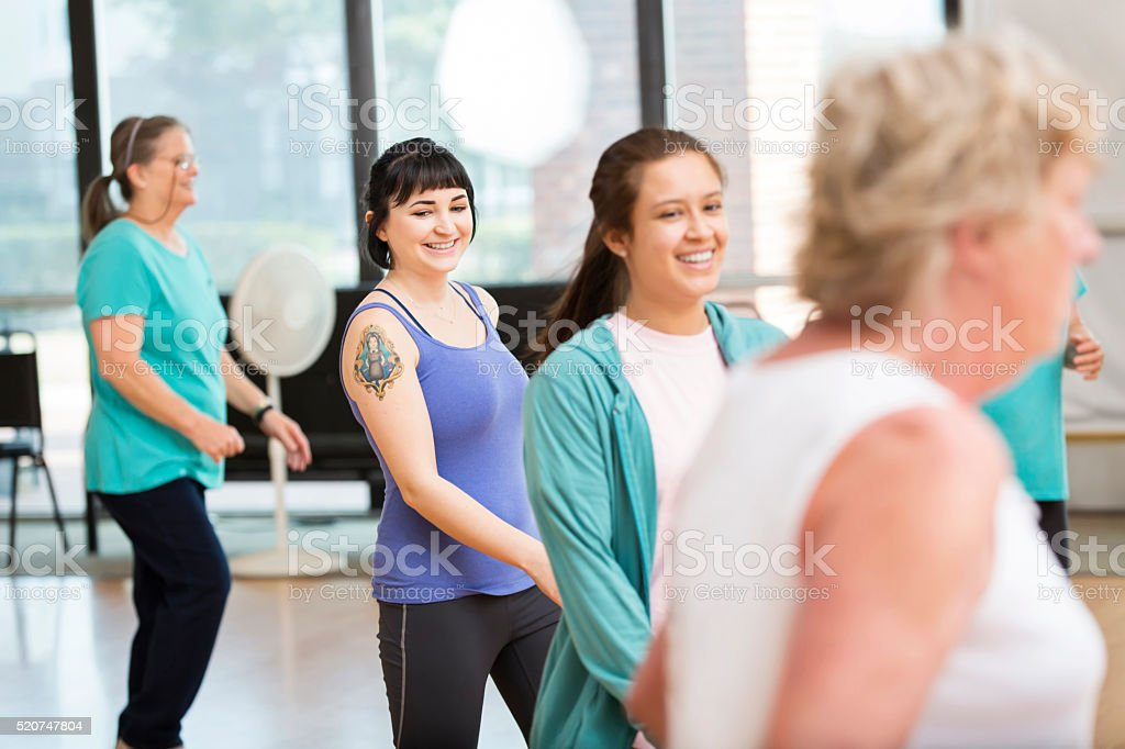 Diverse group of women have fun line dancing stock photo