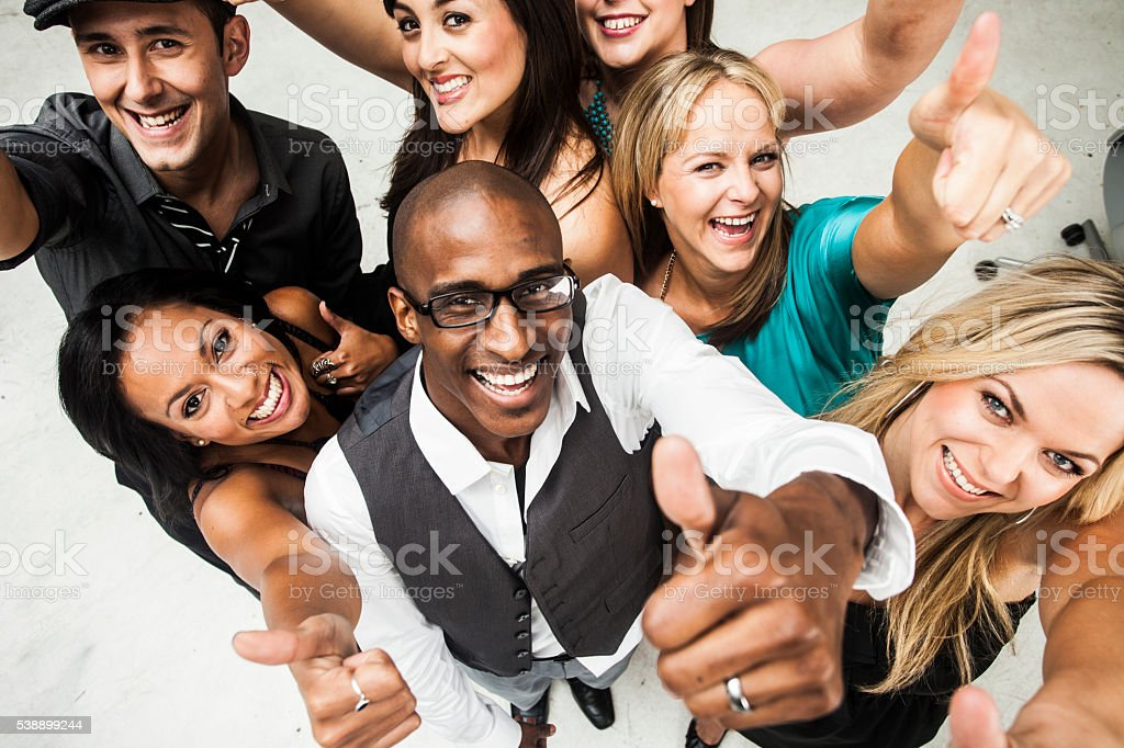 Diverse Group of Young Adults Giving Thumbs Up stock photo