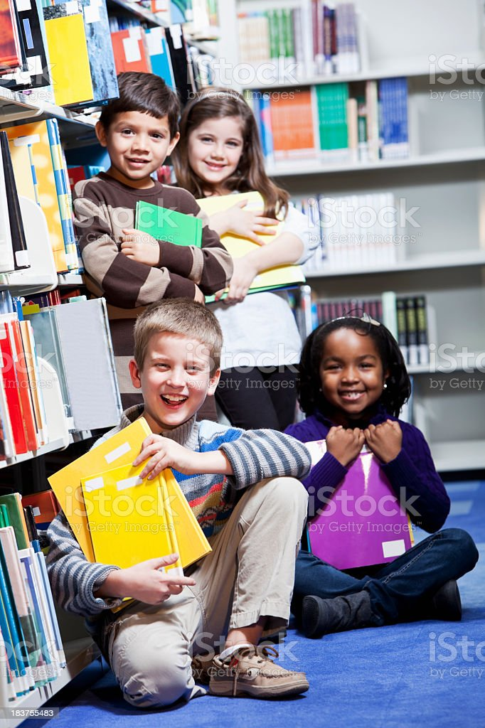 Diverse group of young children in library stock photo