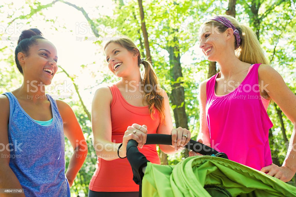 Diverse group of young moms exercising together in park stock photo