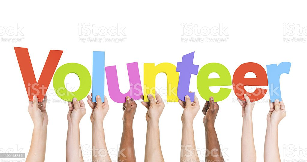 Diverse Hands Holding The Word Volunteer stock photo