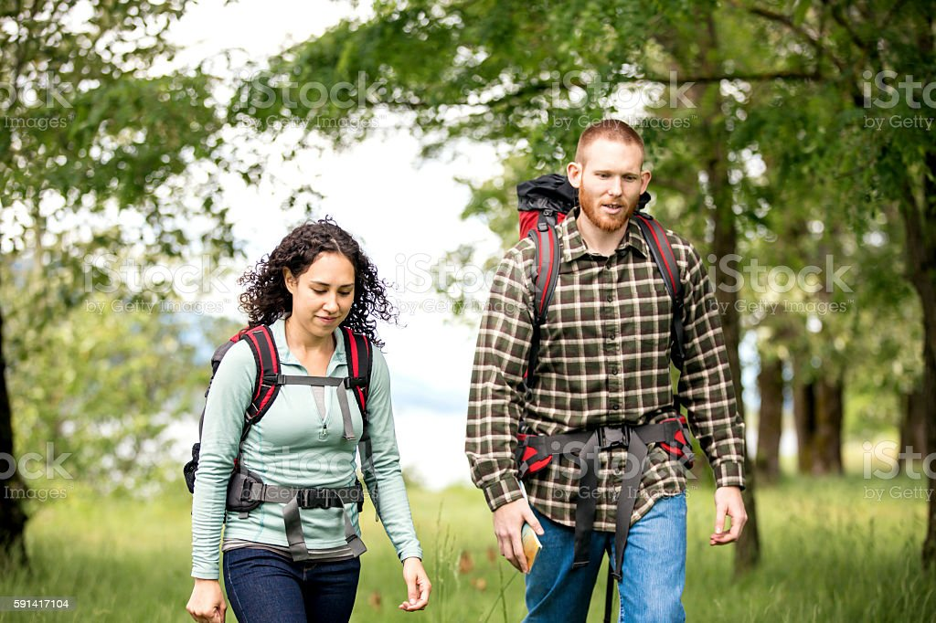 Diverse heterosexual couple hiking together stock photo