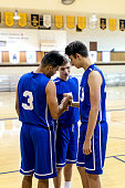 Diverse high school basketball team during a team huddle