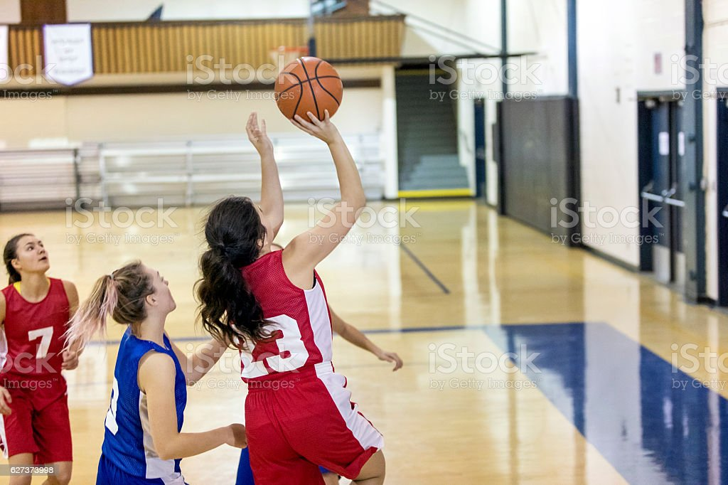 Diverse high school female basketball team playing a game stock photo