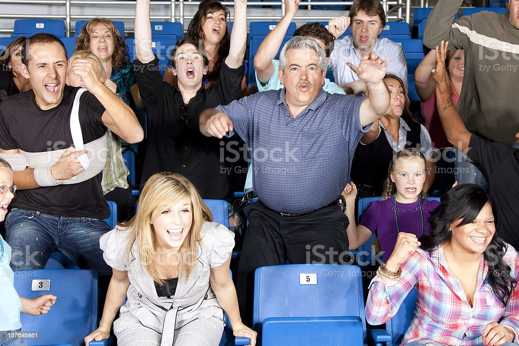 Diverse large group of excited people cheering at a game stock photo