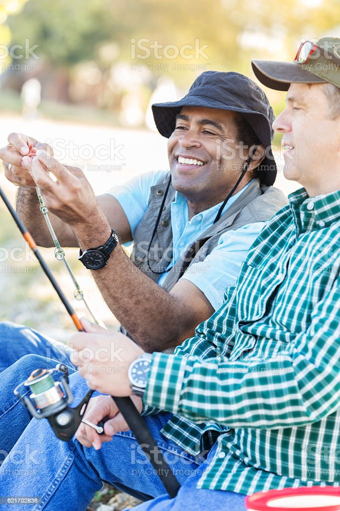 Diverse male friends fish together stock photo