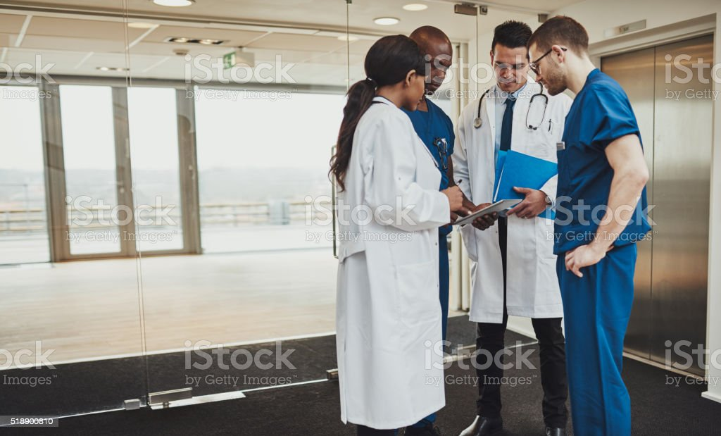 Diverse medical team consulting on a patient stock photo