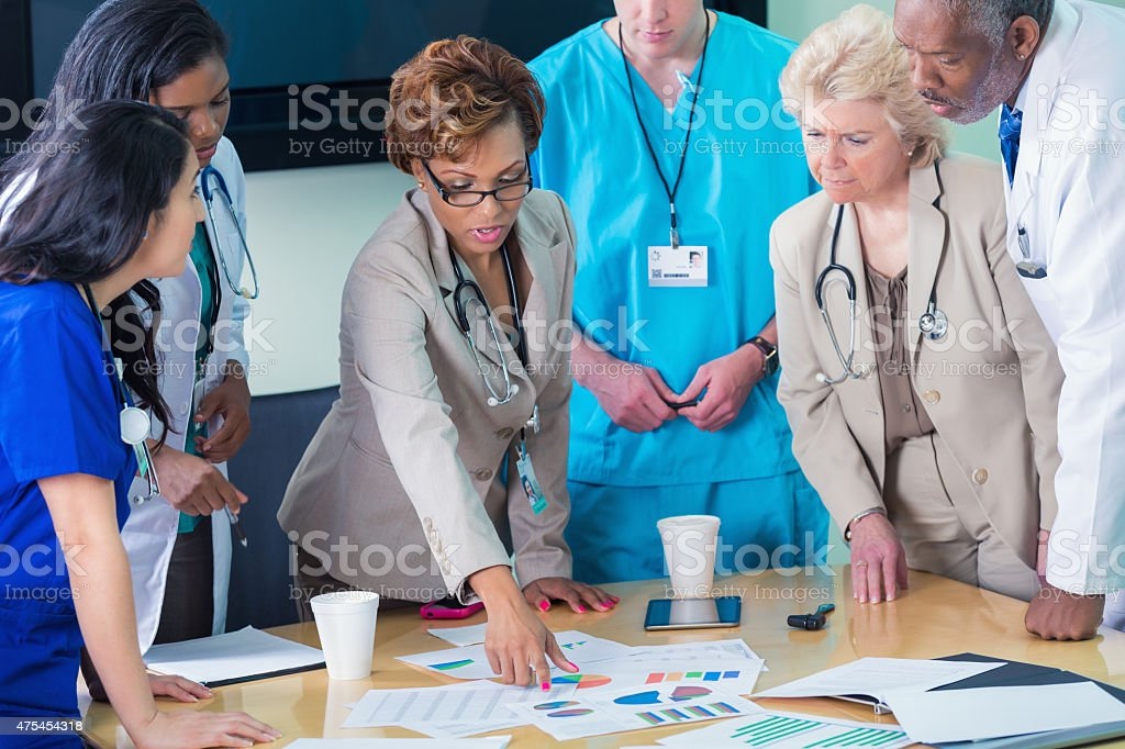 Diverse medical team or board reviewing hospital financial information stock photo