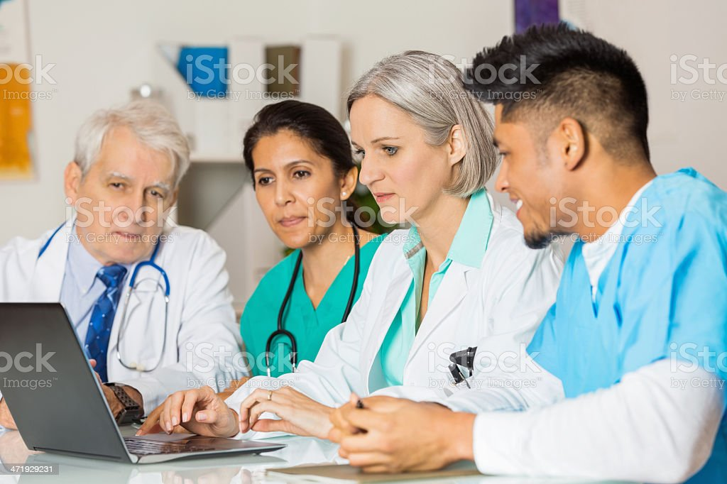 Diverse medical team working together on patient diagnosis royalty-free stock photo