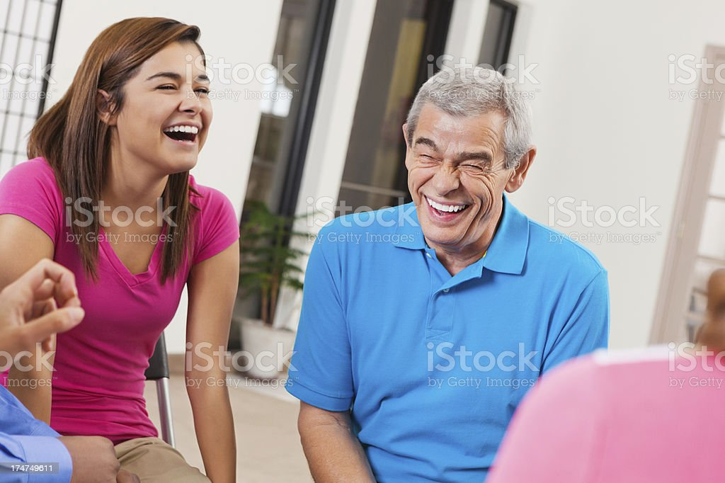 Diverse people laughing together during support group meeting royalty-free stock photo