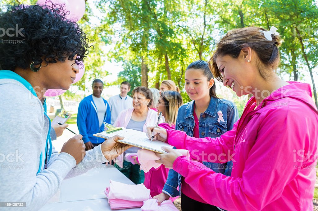 Diverse people registering for charity breast cancer awareness race stock photo