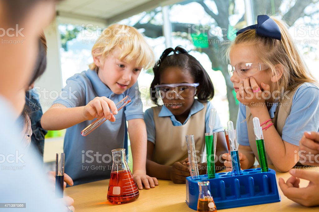 Diverse private elementary school students doing science experiment stock photo