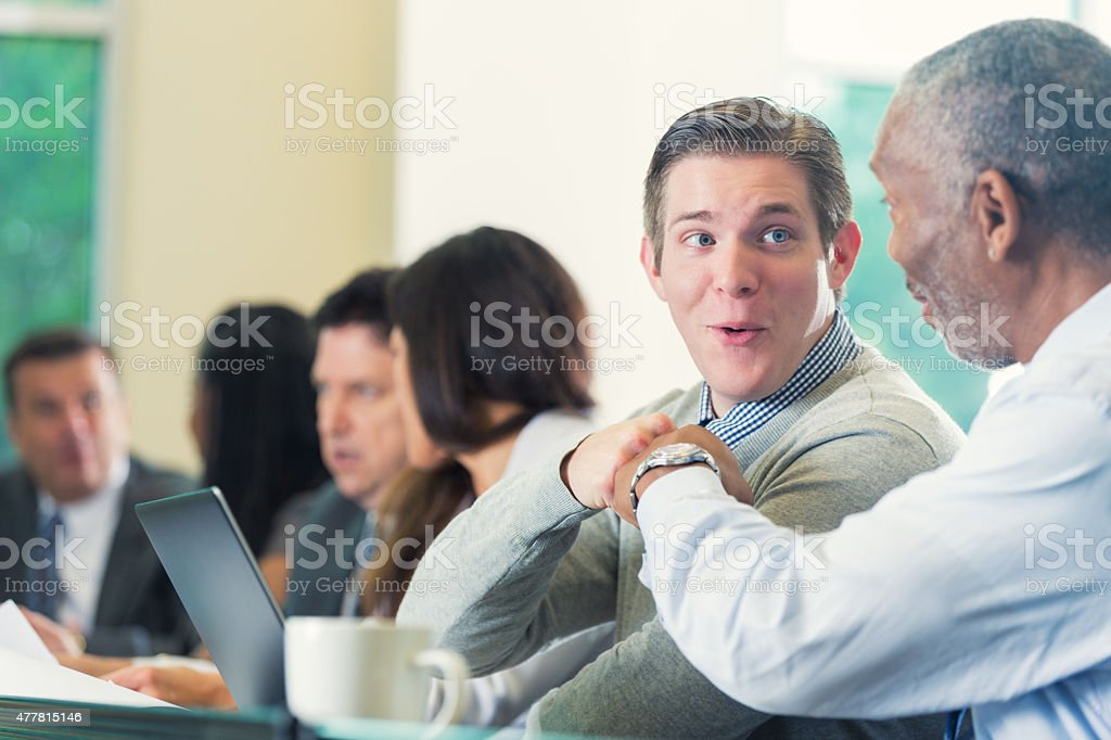 Diverse professional coworkers fist bumping during seminar or conference stock photo