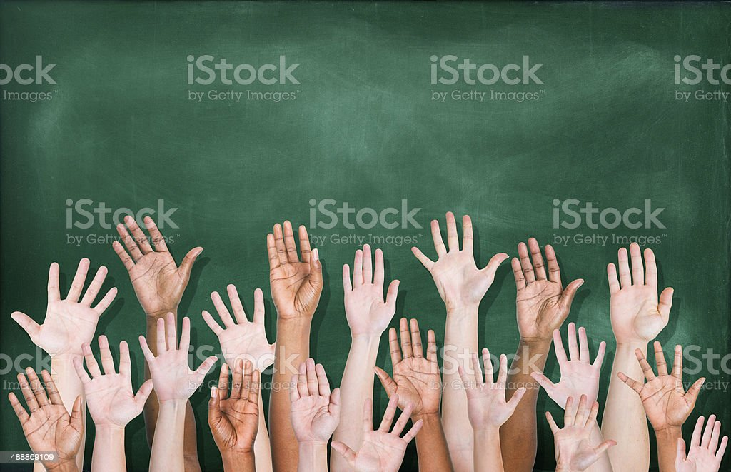 Diverse raised hands in front of blackboard stock photo