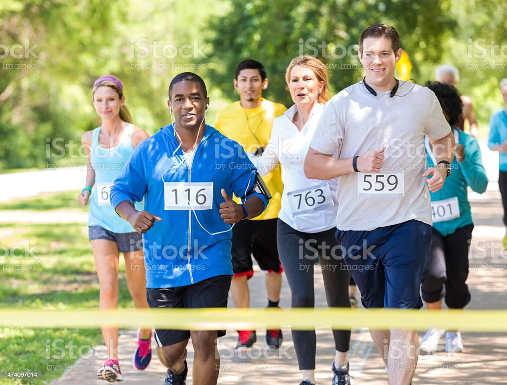 Diverse runners approaching finish line during marathon in park stock photo