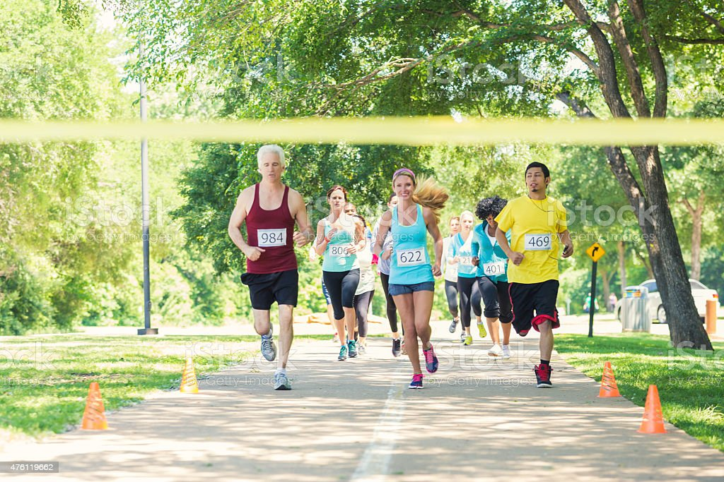 Diverse runners racing excitedly toward finish line during marathon stock photo