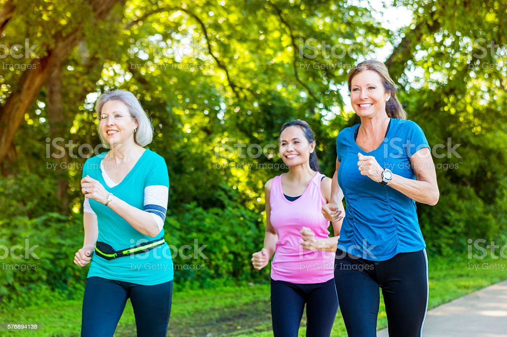 Diverse senior female friends jog on sunny day stock photo