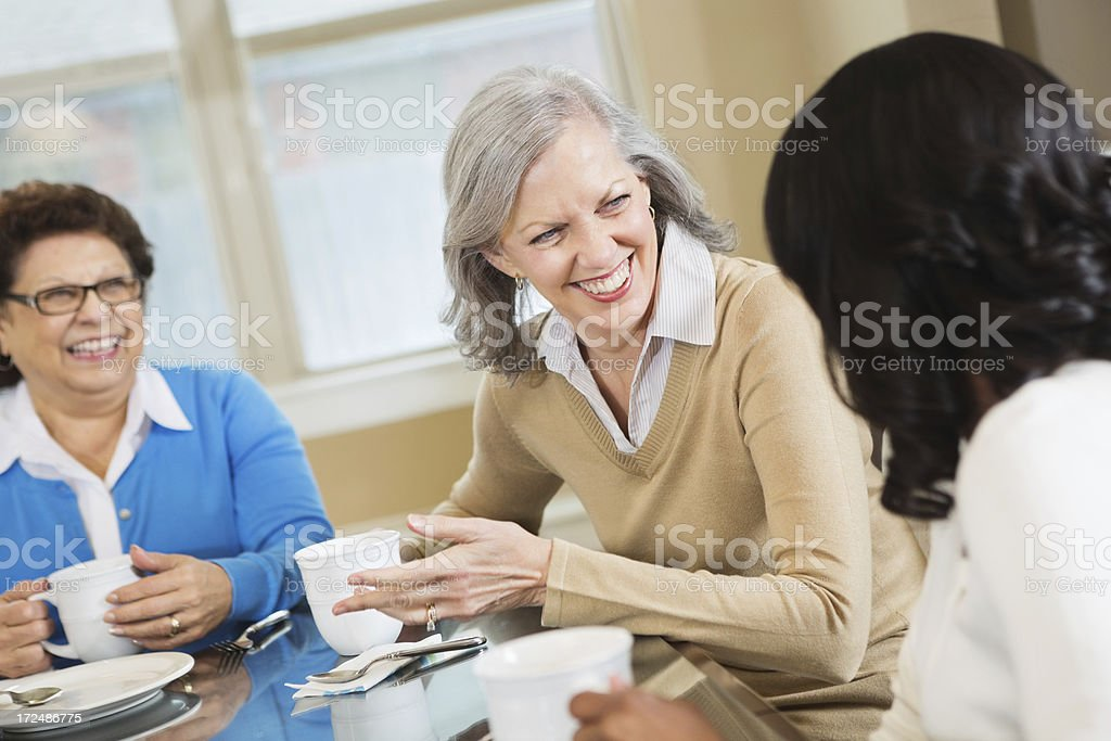 Diverse senior women having coffee together at home royalty-free stock photo