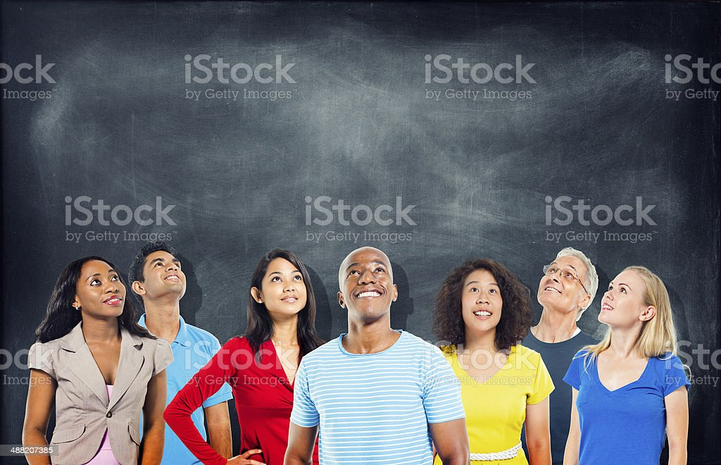 Diverse Students Looking Up With Blackboard stock photo