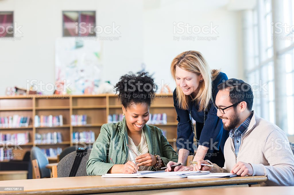 Diverse study group of adults working in large college library stock photo
