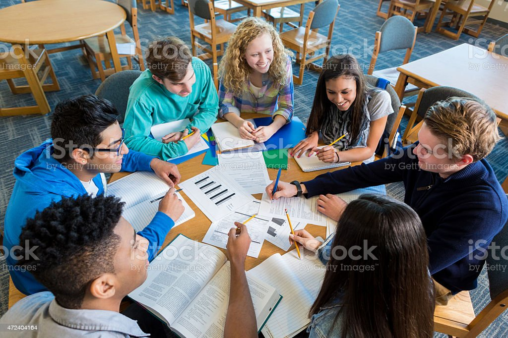 Diverse study group of teenagers studying together in library stock photo