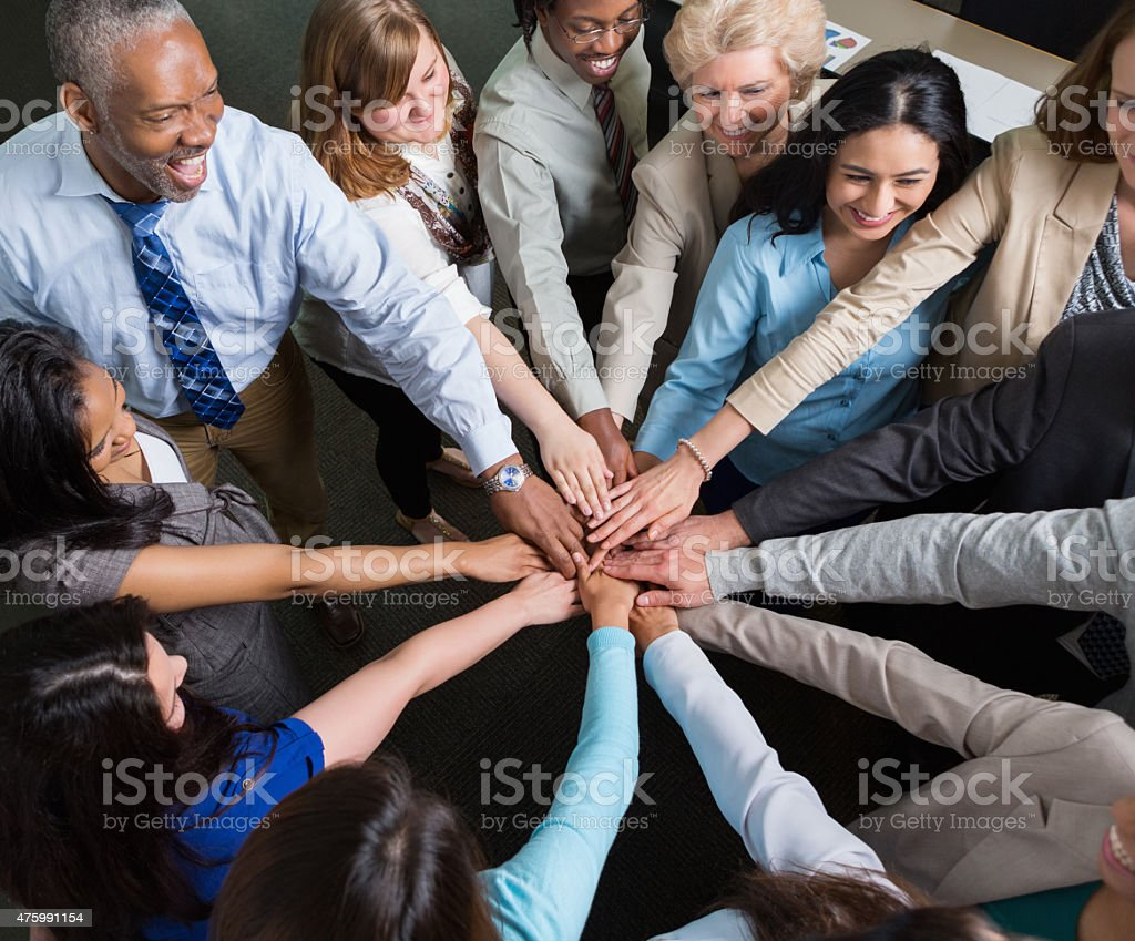 Diverse team of professionals with hands in teamwork huddle stock photo