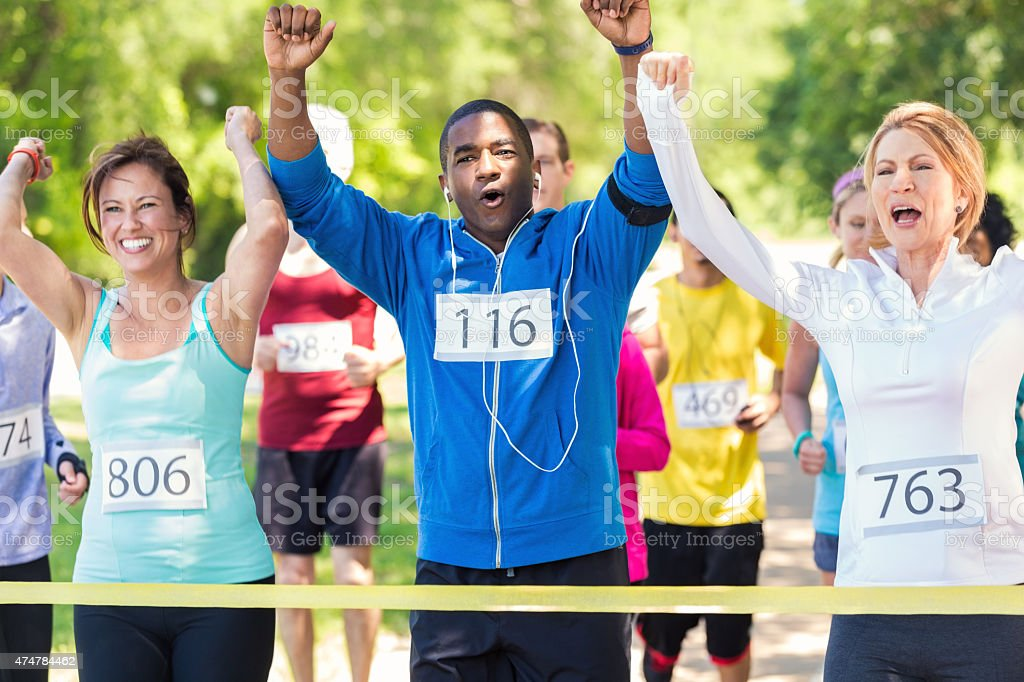 Diverse team of runners celebrating while crossing race finish line stock photo