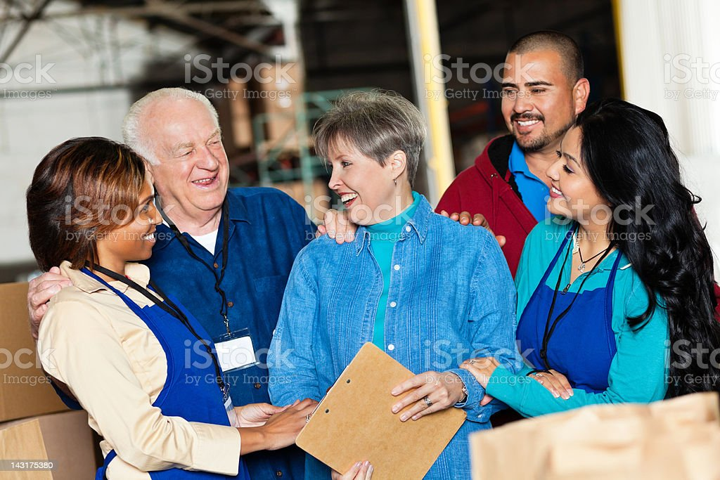 Diverse team of volunteers enjoying time together at donation facility royalty-free stock photo